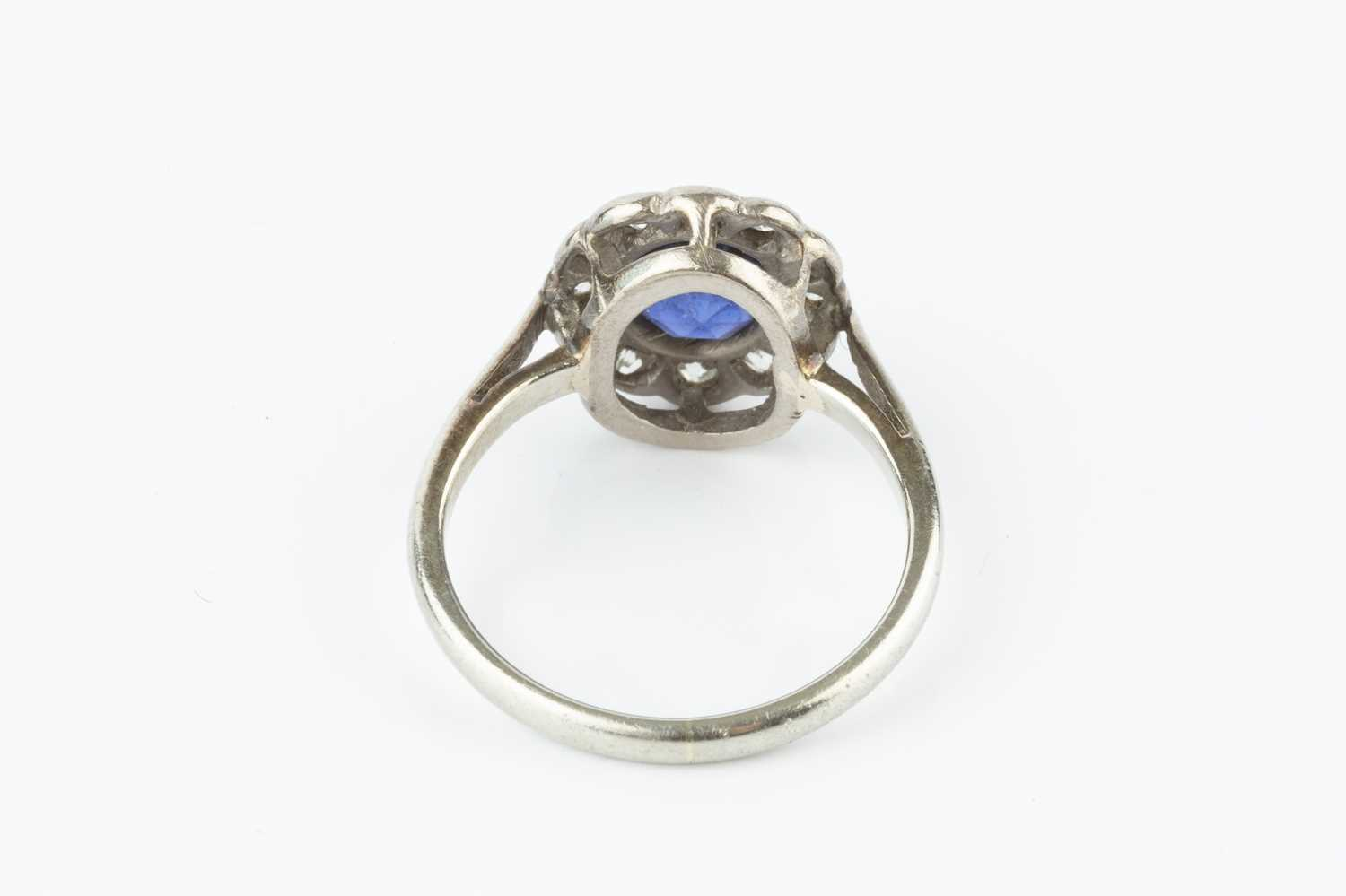A sapphire and diamond cluster ring, the oval mixed-cut sapphire collet set within a border of old - Image 3 of 3