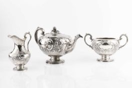 An early Victorian silver three piece tea service, embossed and chased with flowering foliage and '