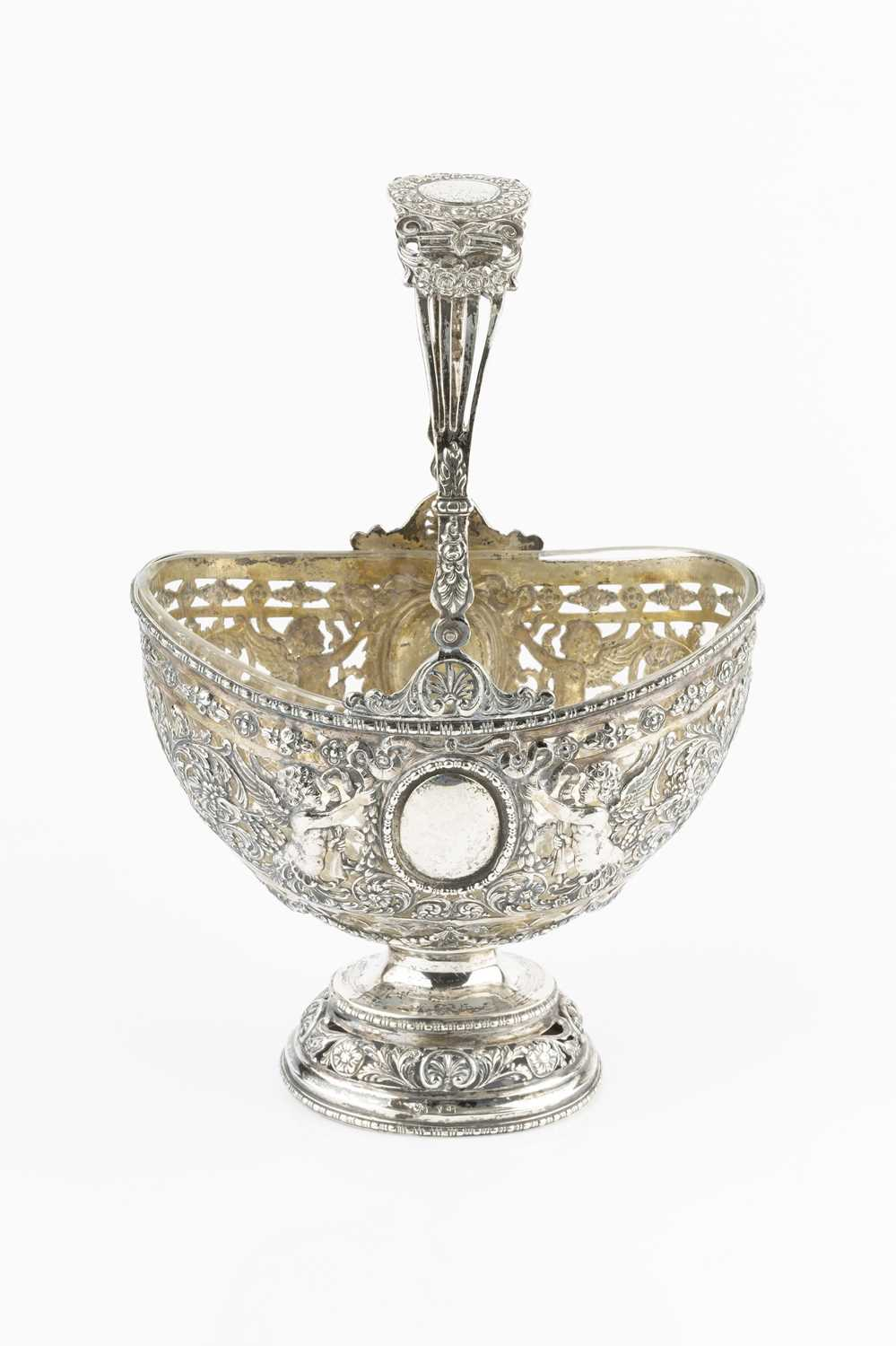 A late 19th century Hanau silver basket, of swing handled oval form, pierced and embossed with putti