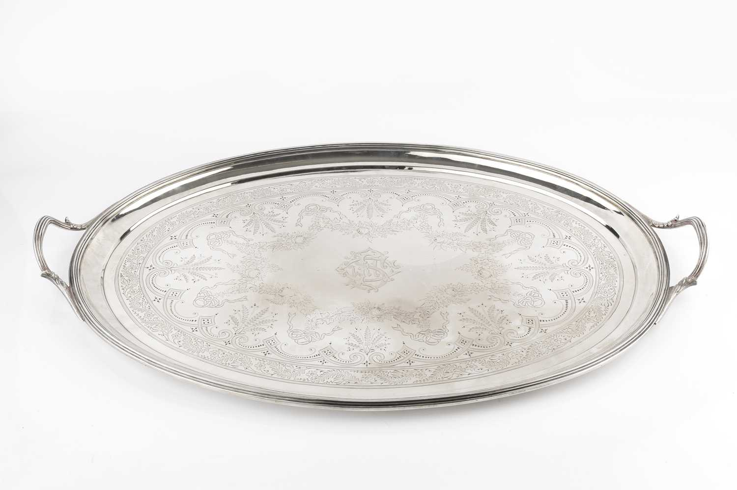 A late Victorian silver twin handled oval tea tray, with reeded border and handles, engraved with