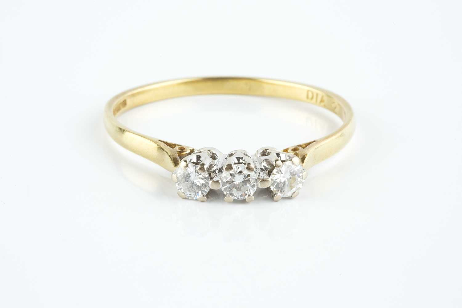 A diamond three stone ring, the round brilliant-cut diamonds in claw setting, 18ct gold mounted,