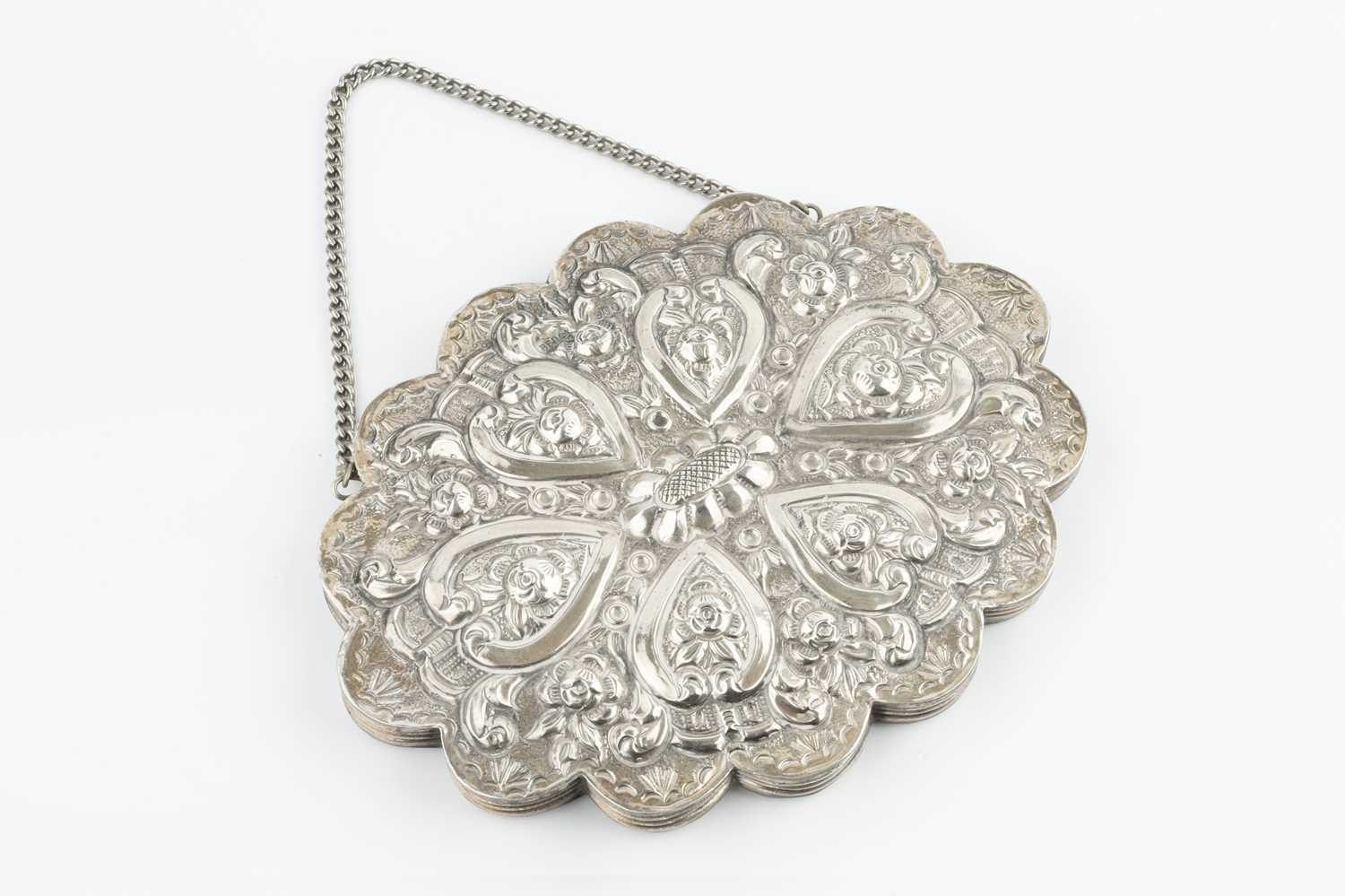 A Continental silver small hanging mirror, of lobed oval outline, embossed with flowers and foliage,