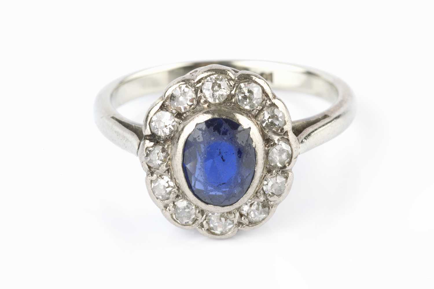 A sapphire and diamond cluster ring, the oval mixed-cut sapphire collet set within a border of old