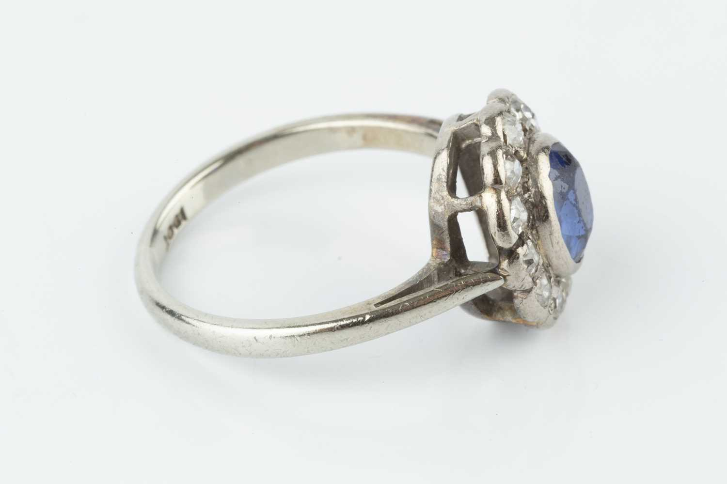 A sapphire and diamond cluster ring, the oval mixed-cut sapphire collet set within a border of old - Image 2 of 3