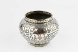 An eastern white metal overlaid brass vase, engraved with stylised foliage and script, within