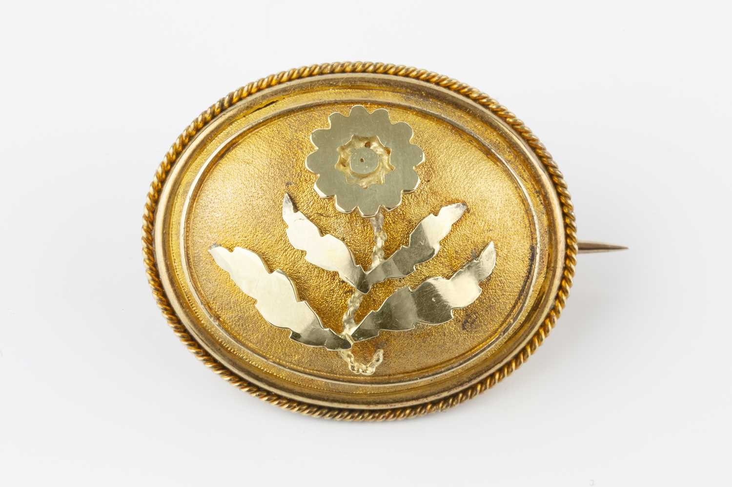 A Victorian panel brooch, the convex oval panel applied with a floral spray to a textured ground,
