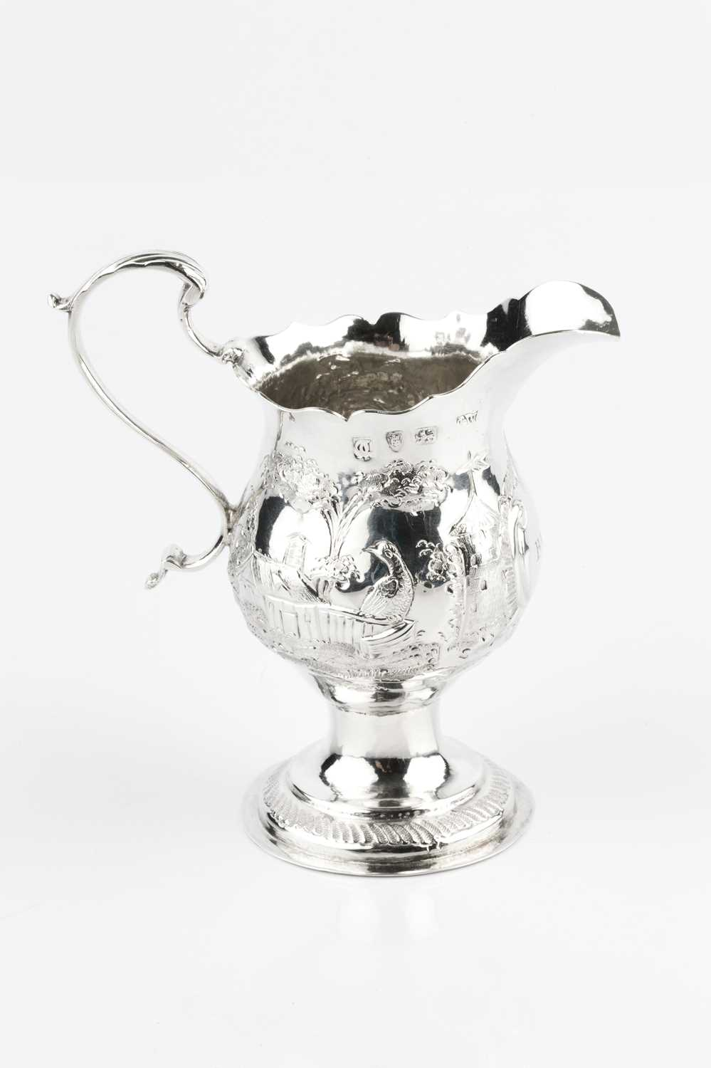 A George III silver cream jug, with baluster body embossed and engraved with a continuous village