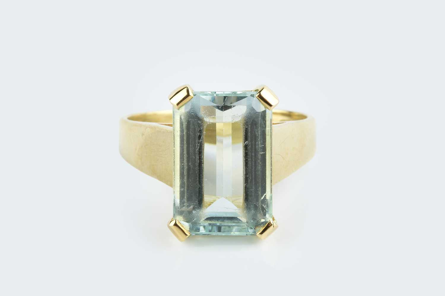 An aquamarine single stone ring, the rectangular step-cut aquamarine with canted corners, in four