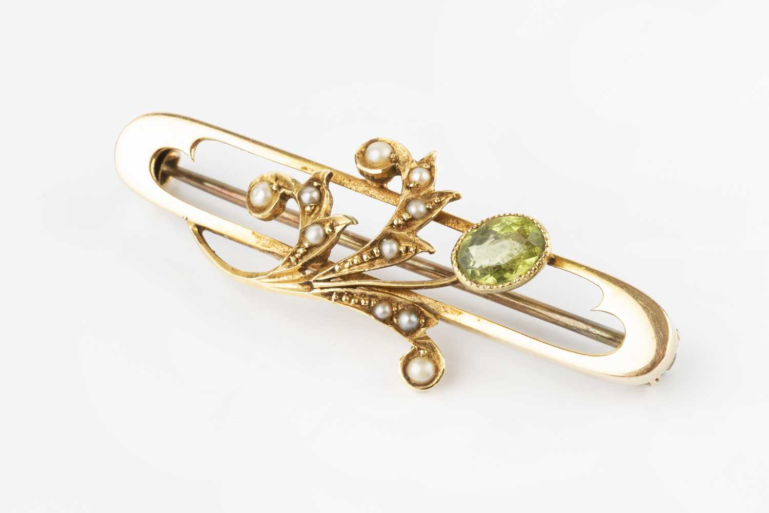 A peridot and half pearl panel brooch, the elongated oval openwork panel applied with a foliate - Image 2 of 3