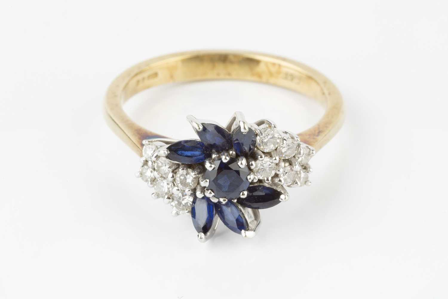 A sapphire and diamond cluster ring, designed as an abstract spray of circular mixed-cut and