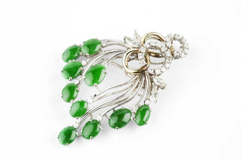 A jade and diamond spray brooch/pendant, designed as a tiered wirework spray of oval jade