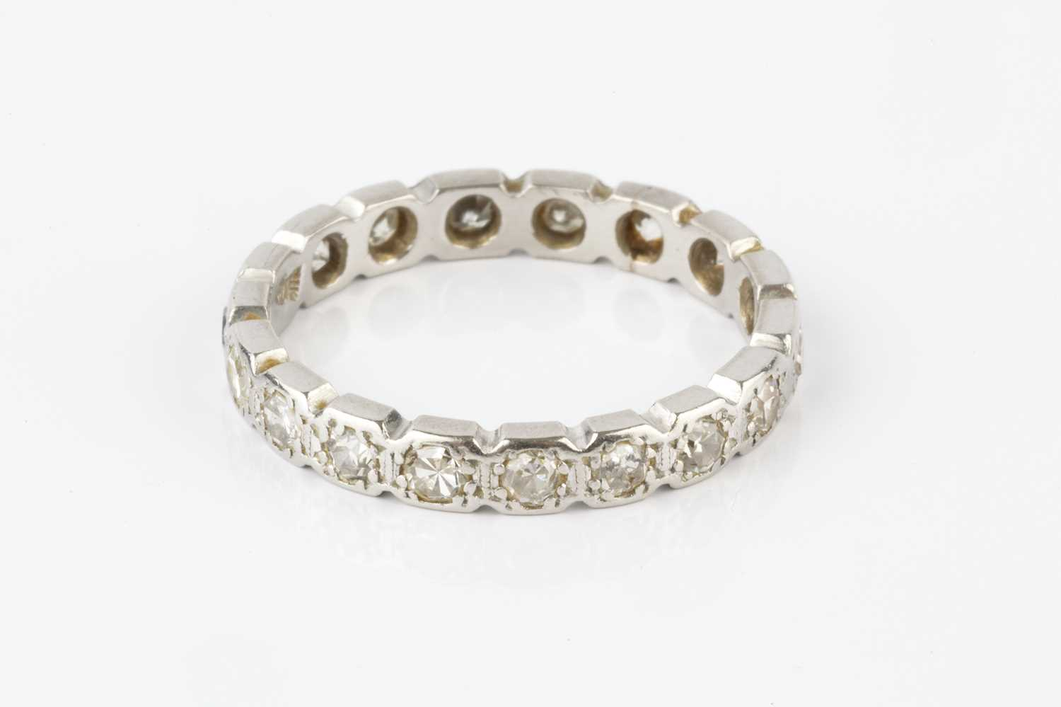 A diamond full hoop eternity ring, designed as a line of geometric settings, each with a single-