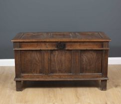 An 18th century and later oak coffer with triple panelled lid and front, standing on stile feet,