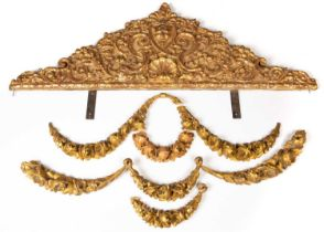 A gilt pressed metal cresting with a wooden backboard, with central pan mask and shell and foliate
