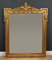 A 19th century gilt wall mirror with outset upper corners and central mask crest with floral and