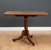 A 19th century mahogany tilt top tripod table with turned column support and reeded splaying legs on