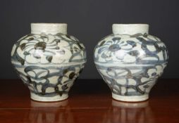 A pair of antique South East Asian jars decorated with scrolls and flowers, 20.5cm diameter x 22cm