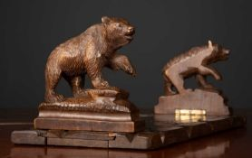 A stained wooden black forest carved adjustable book stand with bears to either end, 34cm wide x