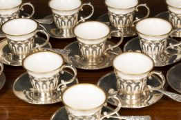 A set of twelve white metal and porcelain espresso coffee cups with gilt line ornament to the