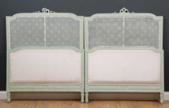 A pair of green painted single beds with caned inset panelsCondition report: One inner caned panel