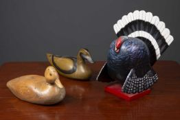 An old striped pine decoy duck with glass eyes, rotating head and lead weight beneath, 33cm long