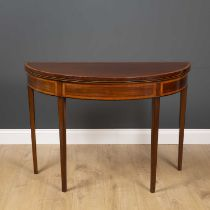 A George III mahogany demi lune fold over tea table with satinwood crossbanded decoration and square