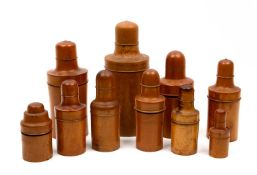 A group of ten 19th century and later turned boxwood bottle cases with screw lids, seven with