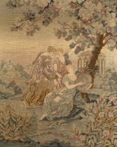 A framed needlework panel depicting three classical maidens beneath a fruit tree and by a temple,