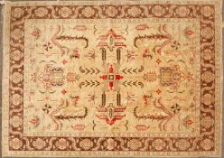 An Oriental dark cream ground small carpet with stylized foliate motifs to the central field and
