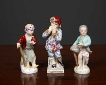 A group of three Berlin porcelain figures of boys one representing Winter, the other two curiously