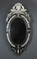 A contemporary Venetian style oval wall mirror with decorative crest, the mirror with engraved slips