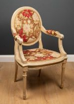 A painted French style armchair with needlework upholstery and turned tapering fluted legs, 57cm