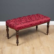 A mahogany stool with turned tapering legs and overstuffed red button upholstered seat, 98cm wide