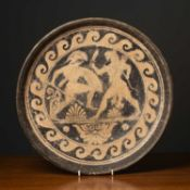 A terracotta dish with classical ornament in the Etruscan style, 40cm diameter bearing a possibly