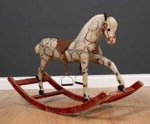 An old small size wood and cloth rocking horse with leather saddle on a red painted base, bearing