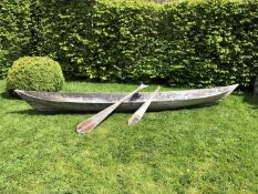 An antique dugout canoe, with two paddles, possibly South American, 328cm long x 43cm wide x 33cm