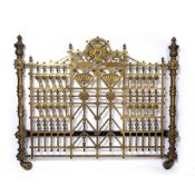 A Victorian brass bedstead in the aesthetic style, decorated with stylised floral roundels and fans,