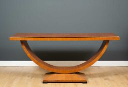 An art deco style walnut side table with arching support and rectangular base with ebonised square