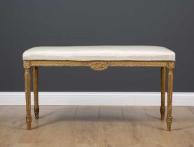A late 19th or early 20th century rectangular gilt window seat with silk upholstery and standing