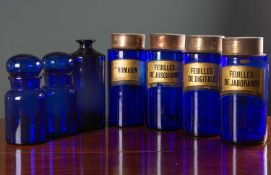 A set of four blue glass cylindrical pharmacy jars with gilt labels and possibly later tin covers,
