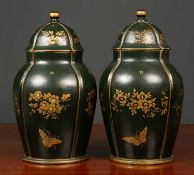 A pair of dark green ground papier mache jars and covers with gilt decoration of butterflies and