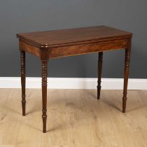A George III fold over tea table with ring turned tapering legs and decorative inlay to the frieze