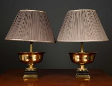 A pair of gilt metal and ebonised table lamps in the form of shallow urns on plinth bases, the table