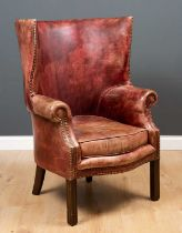 A George II style leather upholstered wing back armchair with curving back, scrolling arms and