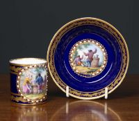 A Sevres porcelain coffee can and saucer on a deep blue ground, with gilt oak leaf banding and