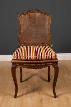 A French walnut side chair with carved frame, caned back and seat and cabriole legs, with striped