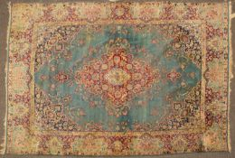 An old Kirman light blue ground carpet with central diamond motif, further decorated with flowers