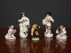 A group of decorative porcelain figurines consisting of two gardeners, two putti one with a sheep