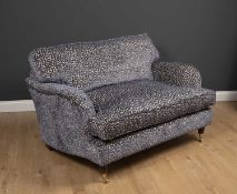 A small modern deep two seater sofa with turned front legs and brass casters, upholstered in lilac