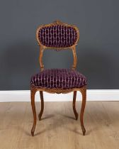 An antique French side chair with carved ornament, overstuffed upholstered back and seat and